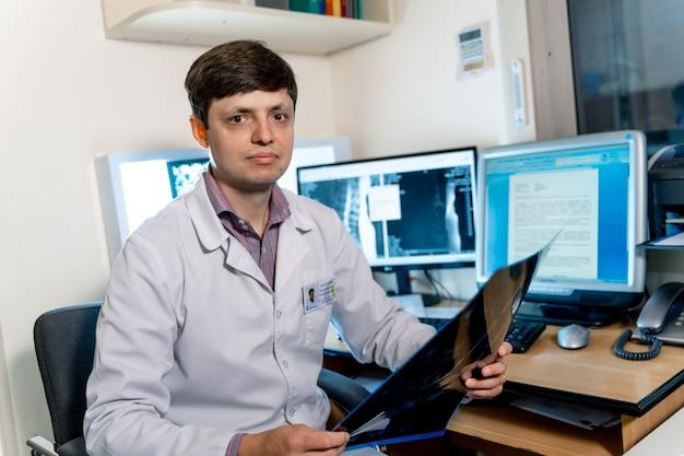 Młody mężczyzna lekarz radiolog loking w aparacie. monitory komputerowe w tle.