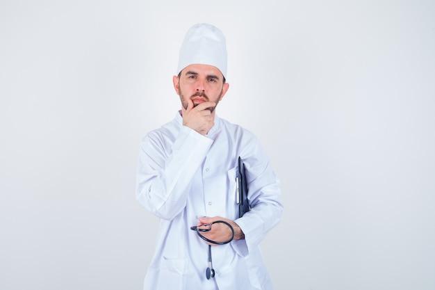 Młody mężczyzna lekarz trzymając schowek, stetoskop, trzymając rękę na brodzie w białym mundurze i patrząc zamyślony. przedni widok.