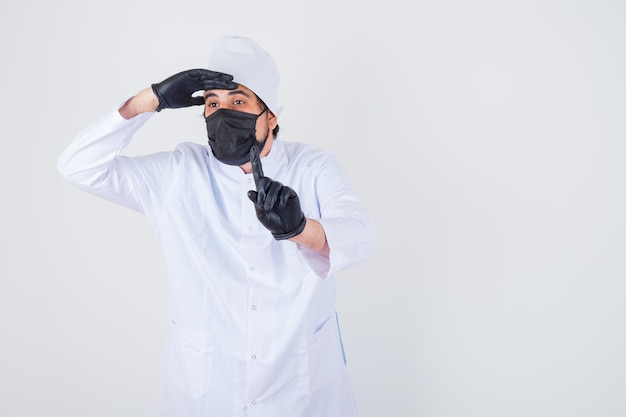 Młody mężczyzna lekarz trzymający rękę na czole, pokazując numer jeden w białym mundurze i patrząc skupiony, widok z przodu.