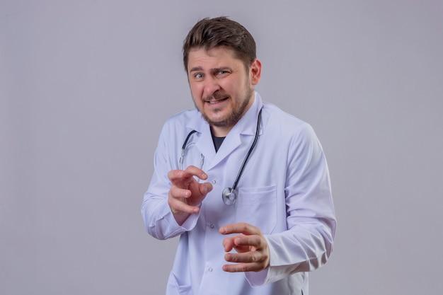 Młody mężczyzna lekarz ubrany w biały fartuch i stetoskop czuje się przestraszony, obawia się czegoś przerażającego, z rękami mówiącymi trzymać się z daleka