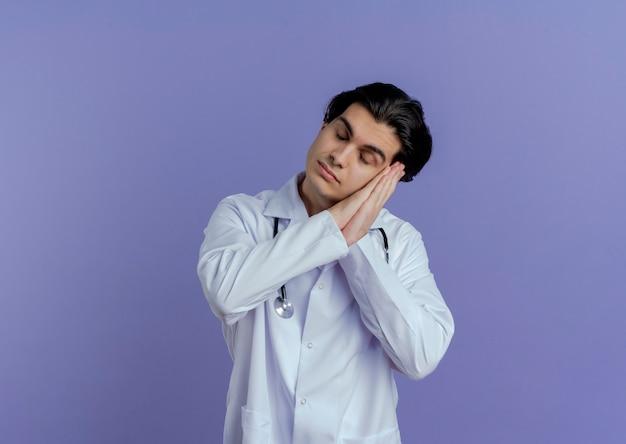 Młody mężczyzna lekarz ubrany w medyczną szatę i stetoskop robi gest snu z zamkniętymi oczami na białym tle
