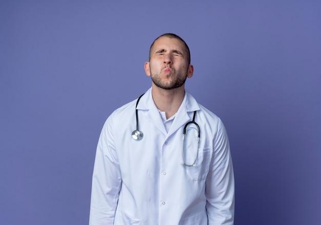 Młody mężczyzna lekarz ubrany w medyczny szlafrok i stetoskop na szyi robi gest pocałunku z zamkniętymi oczami na białym tle na fioletowym tle z miejsca na kopię