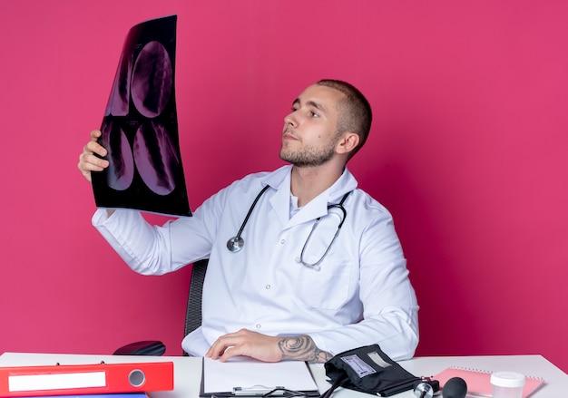 Młody mężczyzna lekarz ubrany w szlafrok medyczny i stetoskop siedzi przy biurku z narzędziami do pracy, trzymając i patrząc na zdjęcie rentgenowskie na białym tle na różowym tle