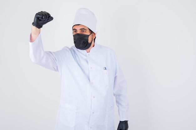 Młody mężczyzna lekarz w białym mundurze pokazujący podnoszącą pięść i patrzący pewnie, widok z przodu.