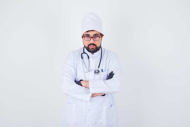Młody mężczyzna lekarz w białym mundurze stoi ze skrzyżowanymi rękami i wygląda pewnie, widok z przodu.