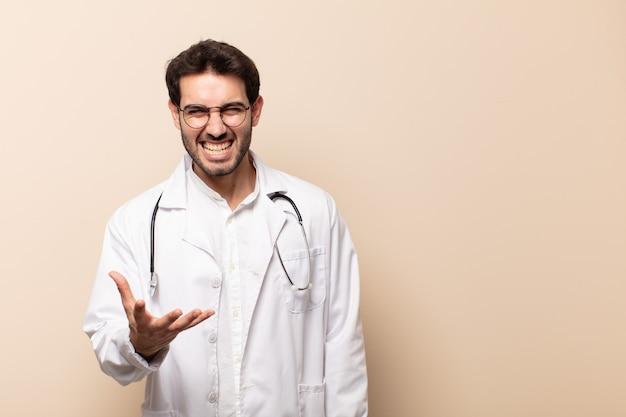 Młody mężczyzna lekarz wyglądający na zły, zirytowany i sfrustrowany krzycząc wtf
