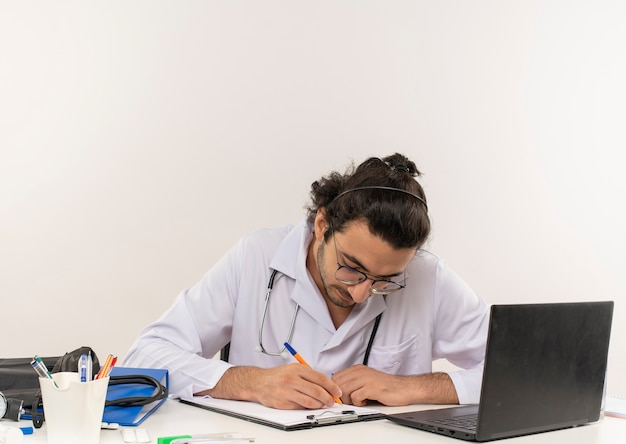 Młody mężczyzna lekarz z okularami medycznymi na sobie szatę medyczną z siedzącym stetoskopem