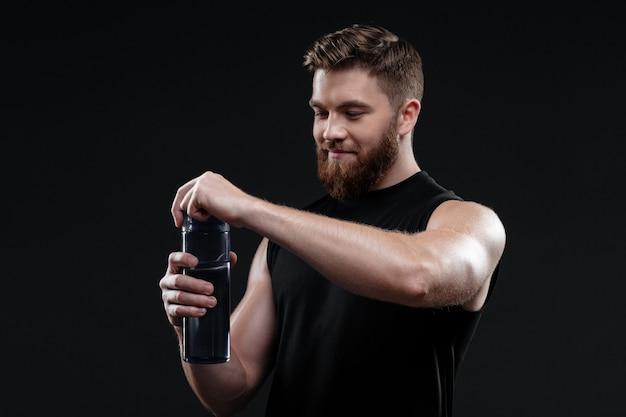 Młody mężczyzna lekkoatletycznego z butelką