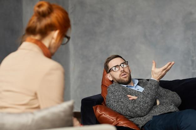 Młody mężczyzna leżący na kanapie i rozmawiający o swoim problemie z psychologiem podczas wizyty