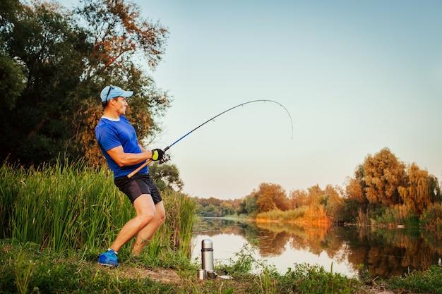 Młody mężczyzna łowi ryby na rzece o zachodzie słońca
