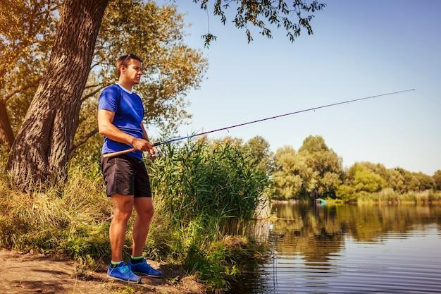 Młody mężczyzna łowiący ryby na brzegu rzeki