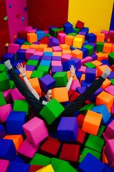 Młody mężczyzna lub chłopiec, ojciec bawi się i skacze w miękkich kostkach w