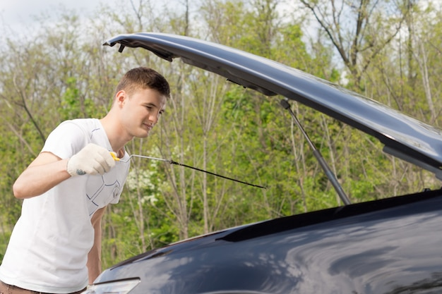 Młody mężczyzna lub mechanik w rękawiczkach sprawdzający olej w silniku samochodu