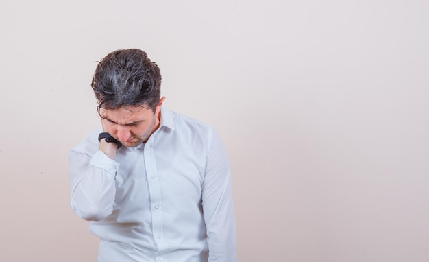 Młody mężczyzna ma ból szyi w białej koszuli i wygląda na zakłopotanego