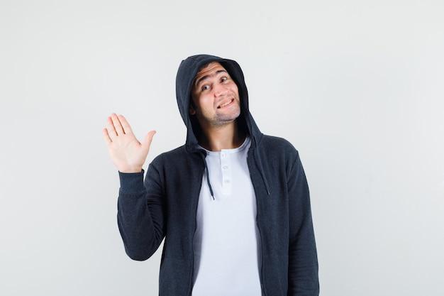 Młody mężczyzna macha ręką, aby pożegnać się w t-shirt, kurtkę i patrząc wesoło, widok z przodu.