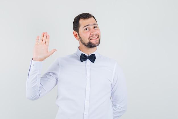 Młody mężczyzna macha ręką, aby się przywitać lub pożegnać w białej koszuli i wyglądający wesoło. przedni widok.
