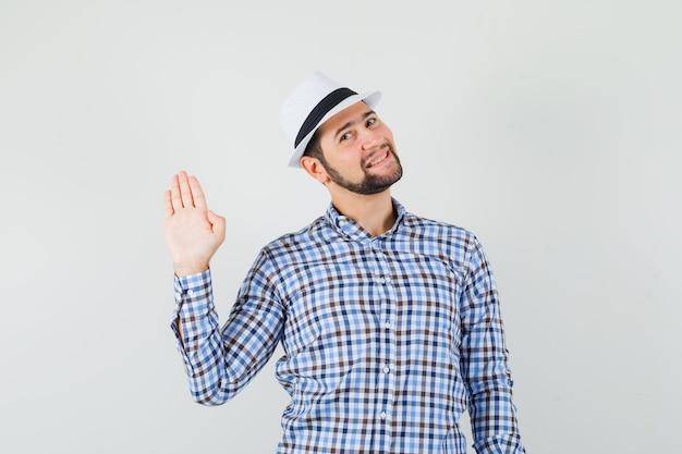 Młody mężczyzna macha ręką, by się przywitać lub pożegnać w kraciastej koszuli, kapeluszu i wesołym wyglądzie. przedni widok.