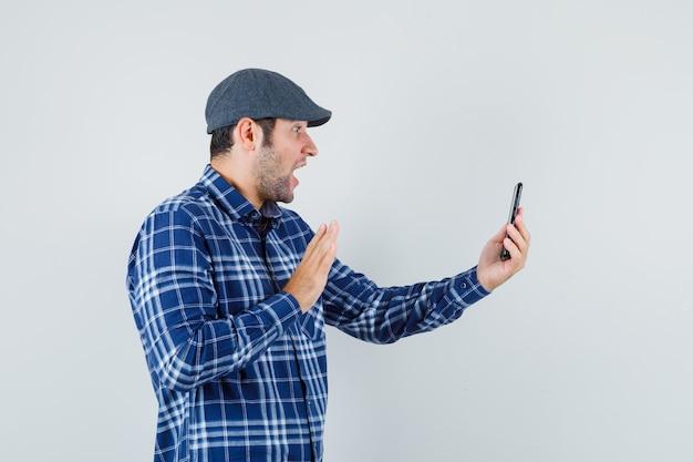 Młody mężczyzna macha ręką na czacie wideo w koszuli, czapce i patrząc wesoło. przedni widok.