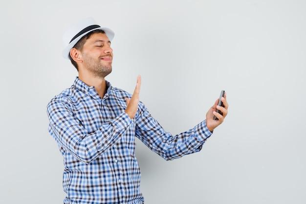 Młody mężczyzna macha ręką na czacie wideo w kraciastej koszuli