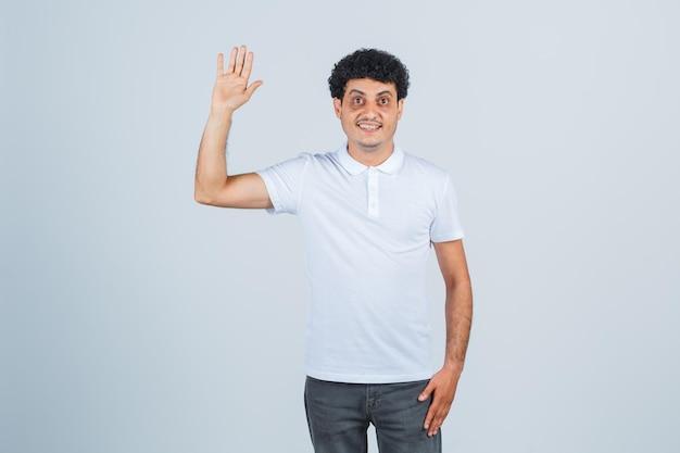 Młody mężczyzna macha ręką na powitanie w białej koszulce, spodniach i patrząc pewnie, widok z przodu.