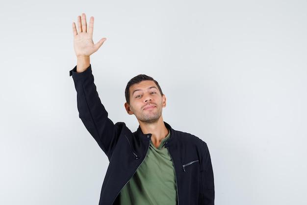 Młody mężczyzna macha ręką na powitanie w koszulce, kurtce i patrząc wesoło, widok z przodu.