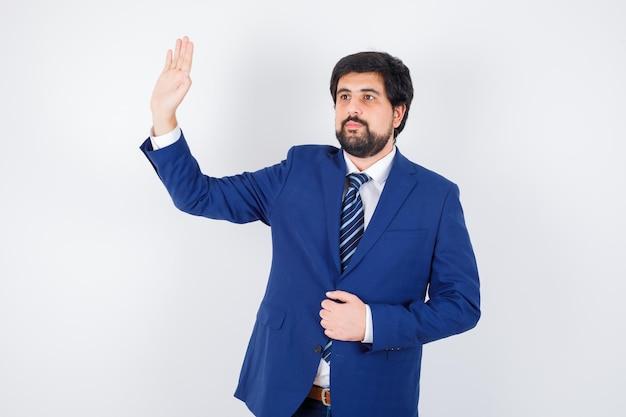 Młody mężczyzna macha ręką na powitanie w koszuli, kurtce, widoku z przodu krawata.