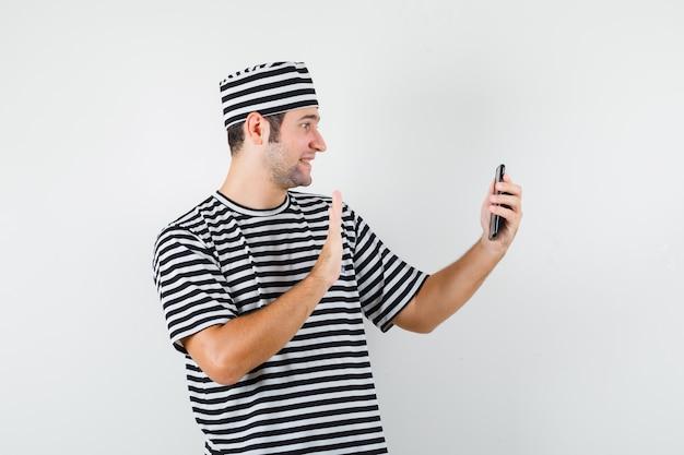 Młody mężczyzna macha ręką na rozmowę wideo w t-shirt, kapelusz i patrząc wesoło, widok z przodu.