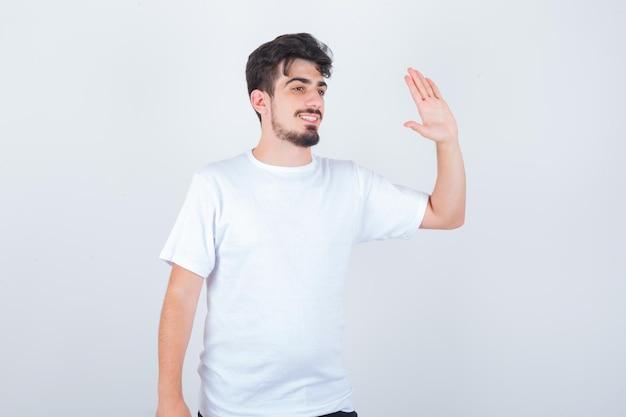 Młody mężczyzna machający ręką na pożegnanie w koszulce i wyglądający radośnie