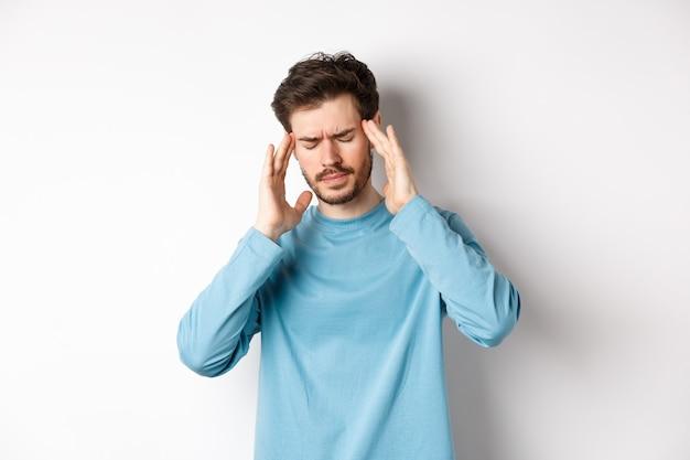 Młody mężczyzna mający ból głowy lub kaca, dotykający skroni głowy i marszczący brwi, mdłości z powodu migreny, stojący na białym tle
