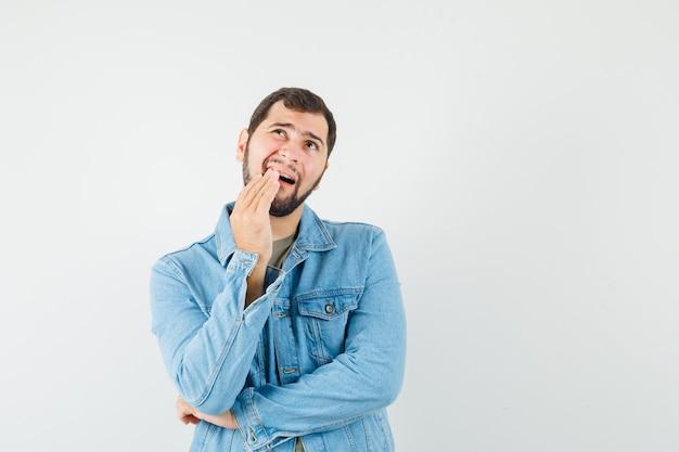 Młody mężczyzna mający bolesny ból zęba w kurtce t-shirt i wyglądający na niewygodnego