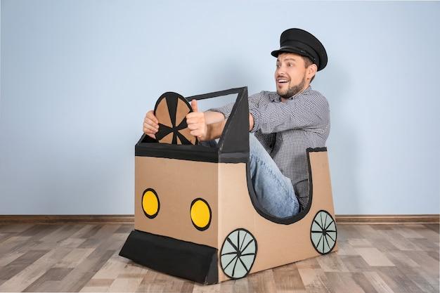 Młody mężczyzna marzący o kupnie własnego samochodu podczas zabawy kartonowym samochodem w pomieszczeniu