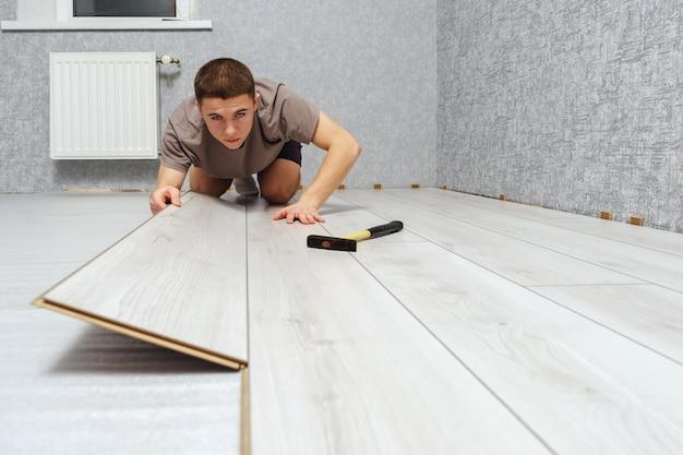 Młody mężczyzna mechanik kładzie drewniany panel podłogi laminowanej w pomieszczeniu. podłogi laminowane, miejsce na kopię. selektywna ostrość