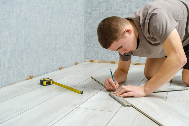 Młody mężczyzna mechanik zaznacza drewniany panel ołówkiem i linijką przed cięciem. podłogi laminowane, miejsce na kopię.