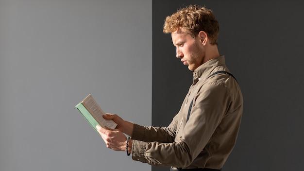 Młody mężczyzna model czytania widok z boku