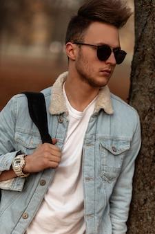 Młody mężczyzna model w stylowej dżinsowej niebieskiej kurtce pozowanie w parku
