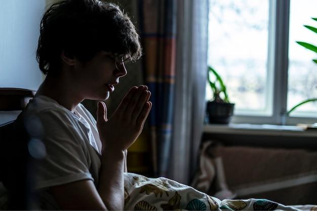 Młody mężczyzna modli się w łóżku w domu przy oknie b