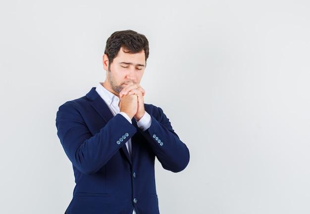 Młody mężczyzna modli się z założonymi rękami w garniturze i wygląda z nadzieją. przedni widok.