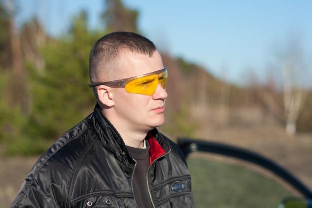 Młody mężczyzna mody z postawą i nowoczesnymi zepsutymi okularami