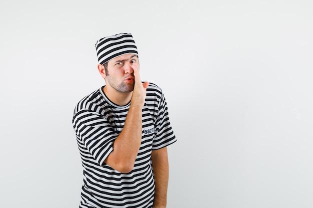 Młody mężczyzna mówi tajemnicę za ręką w t-shirt, widok z przodu kapelusz.