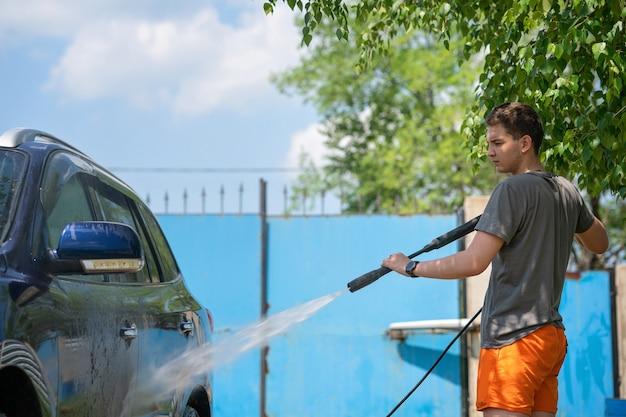 Młody mężczyzna myjący samochód bezdotykowym strumieniem wody pod wysokim ciśnieniem w samoobsługowej myjni samochodowej
