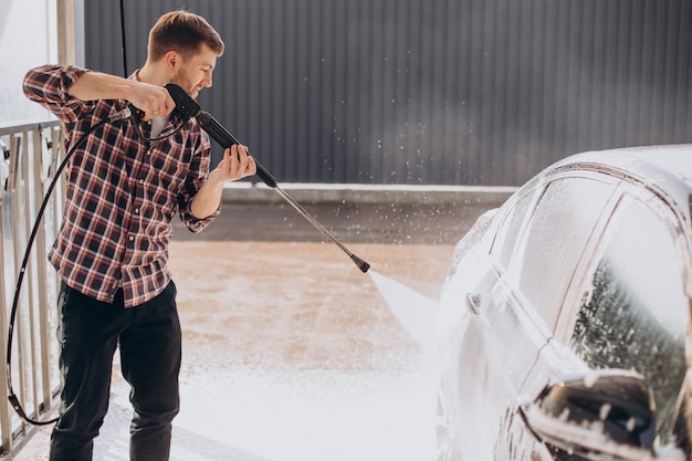 Młody mężczyzna myje samochód w myjni samochodowej