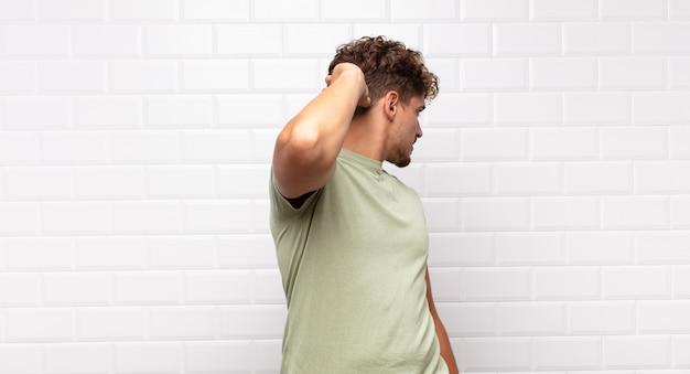 Młody mężczyzna myślący lub wątpiący, drapiąc się po głowie, zdziwiony i zdezorientowany, widok z tyłu lub z tyłu