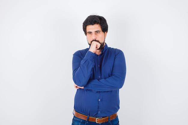 Młody mężczyzna myśli, odwracając wzrok w niebieskiej koszuli i patrząc zamyślony. przedni widok.