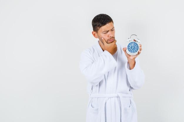 Młody mężczyzna myśli, trzymając budzik w białym szlafroku i patrząc ostrożnie. przedni widok.