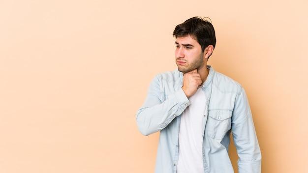 Młody mężczyzna na beżowej ścianie cierpi na ból gardła z powodu wirusa lub infekcji.
