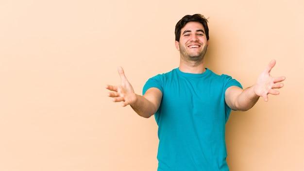 Młody mężczyzna na beżowym tle czuje się pewnie, przytulając aparat.