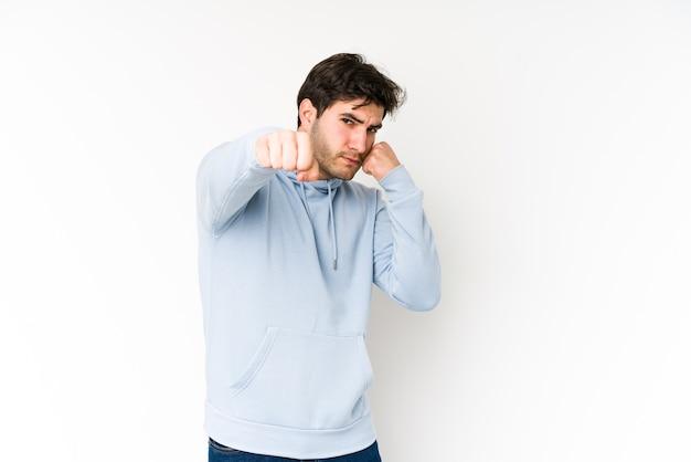 Młody mężczyzna na białej ścianie rzuca cios, gniew, walka z powodu kłótni, boks