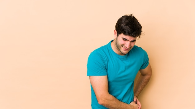 Młody mężczyzna na białym tle na beżowym tle ból wątroby, brzucha.