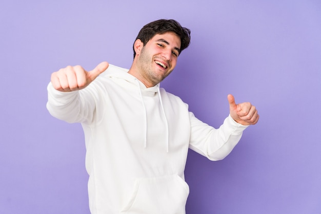 Młody mężczyzna na białym tle na fioletowym tle, podnosząc kciuki do góry, uśmiechnięty i pewny siebie.