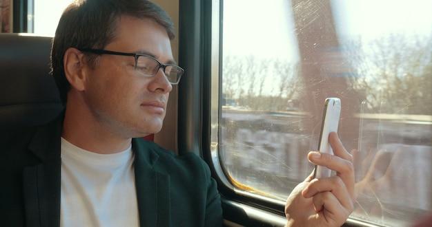 Młody mężczyzna na czacie wideo na komórce w pociągu